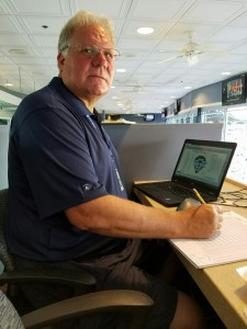"""KeepScore co-founder Thomas """"TJ"""" Lane scores a Pirate game in the booth at PNC Park for Major League Baseball during the 2016 season. His scoring system of choice: why, the KeepScore Baseball/Softball Scorebook, of course."""